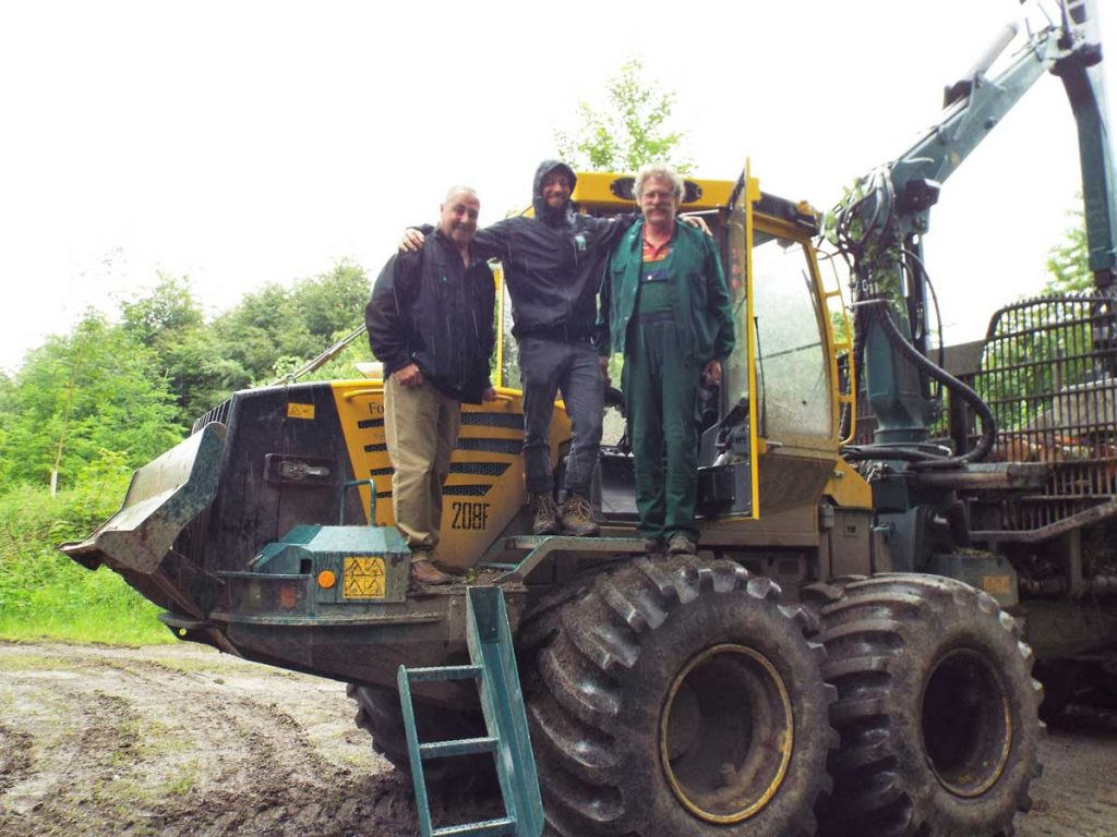 Rab Easton, Patrick Preusch and Klaus Metzler standing on HSM 208F forwarder in the forest