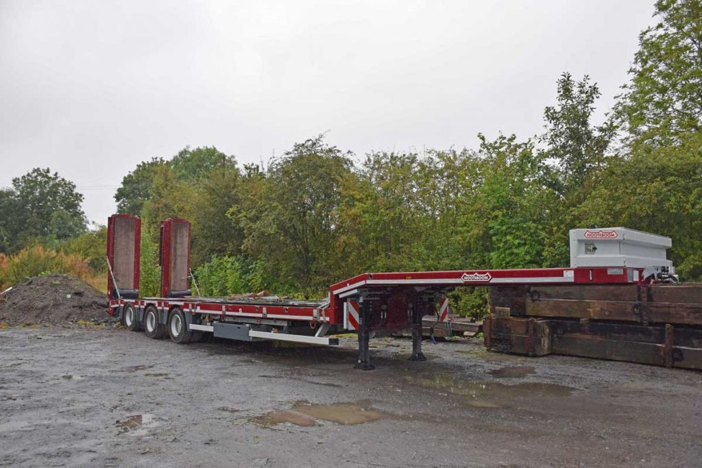 Low loader with 3 axle steering parked in yard