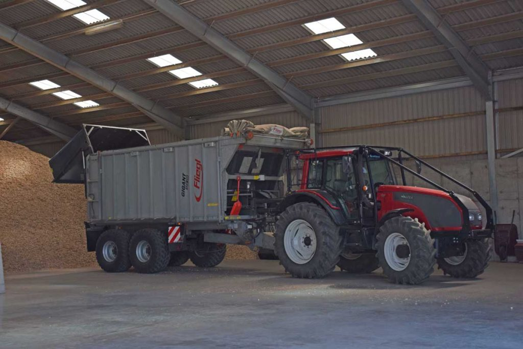Forestry guarded Vatra tractor with a Fliegl push-off 20 tonne trailer unloading wood chips.